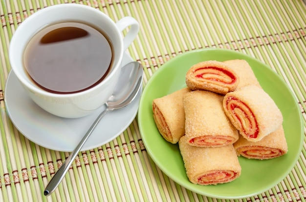 Pâte feuilletée avec de la confiture sur une assiette et une tasse de thé