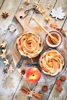 Pâte feuilletée faite maison avec des tranches de pomme en forme de rose cuites au four sur du bois