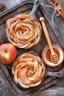 Pâte feuilletée faite maison avec des tranches de pomme en forme de rose cuites dans une poêle en fer sombre