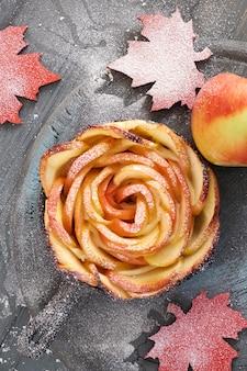 Pâte feuilletée maison avec des tranches de pomme en forme de rose cuites dans une poêle en fer