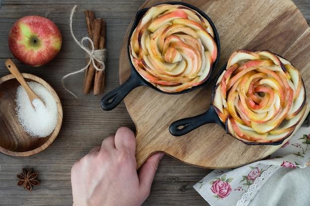 Pâte feuilletée maison avec des tranches de pomme en forme de rose cuites dans des poêles en fer