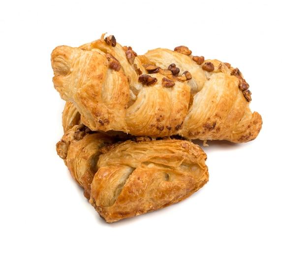Pâte feuilletée tressée sucrée isolée ou pate feuilletee sur fond blanc. pâte phyllo fraîche avec de la confiture à l'intérieur et des noix de macadamia close up