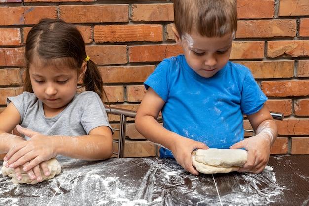 Pâte de fille et de garçon de petits enfants, préparant la pâte pour la cuisson