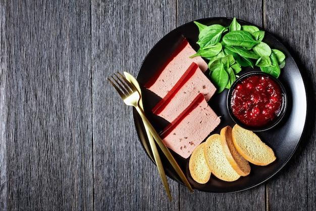 Pâté de foie de canard avec gelée de canneberges sur le dessus sur une assiette noire avec sauce aux canneberges, épinards et croûtons briochés, avec couverts dorés sur fond de bois sombre, gros plan, vue de dessus, espace pour copie