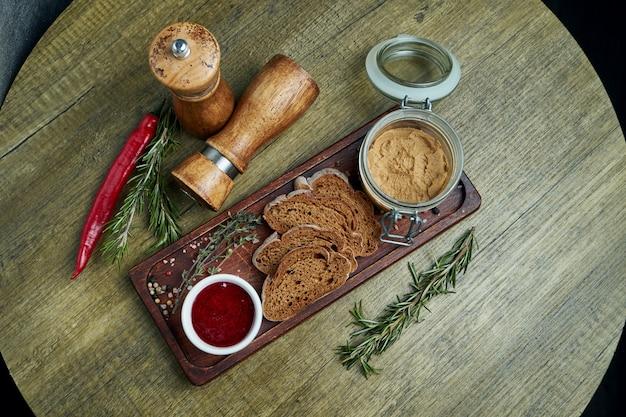 Pâté de foie gras d'oie fait maison avec du pain de seigle et de la confiture sur un plateau en bois. vue de dessus sur la nourriture savoureuse du restaurant. apéritif