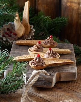 Pâté de foie de poulet fait maison avec des canneberges dans des cuillères sablées comestibles sur une vieille planche à découper en bois