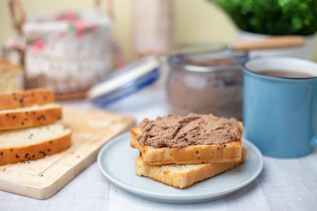 Pâté de foie de poulet fait maison, pain blanc fait maison. petit déjeuner. mise au point sélective, gros plan.
