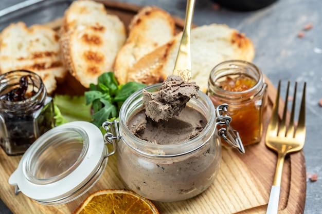 Pâté de foie de poulet frais fait maison avec des morceaux de pain blanc. bruschetta apéritif italien assorti. fond de recette de nourriture. fermer