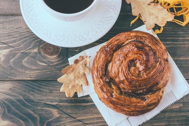 Pâte fraîche bun, tasse de café chaud et feuilles d'automne sur fond en bois. vue de dessus, espace de copie