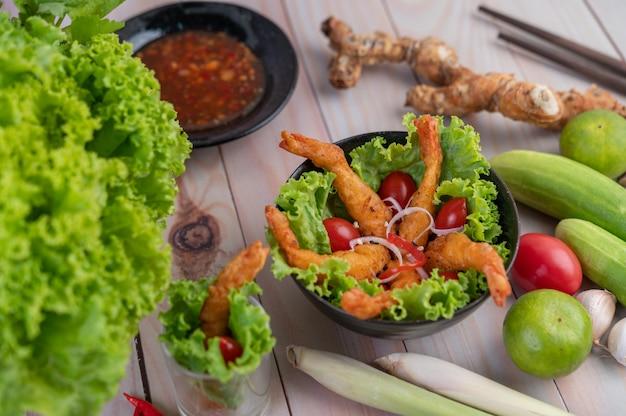 Pâte frite aux crevettes placée sur salade et tomates dans un bol en bois.