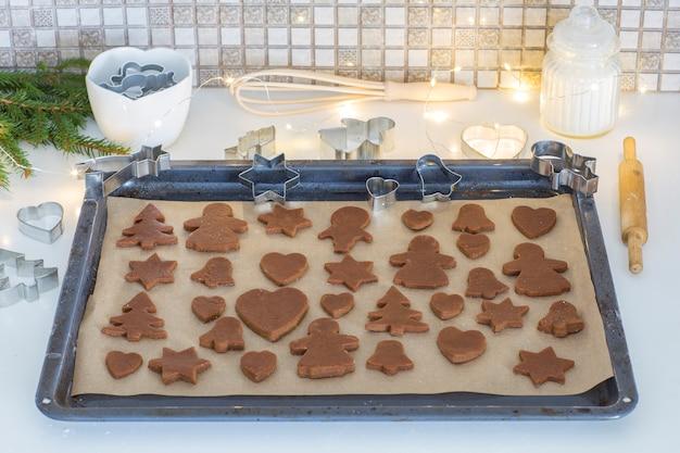 Pâte à gingembre, feston, branches d'épinette, moules à pâtisserie et un rouleau à pâtisserie sont posés sur la plaque de cuisson