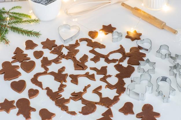 Pâte de gingembre roulée, morceaux de pâte coupés pour biscuits, moules à pâtisserie, rouleau à pâtisserie, branches d'épinette, guirlande