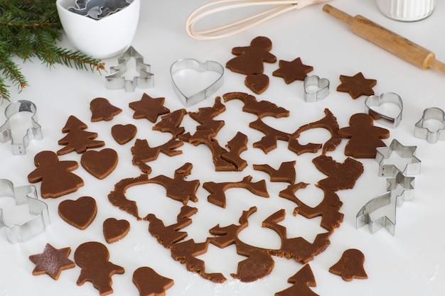 Pâte de gingembre roulée, morceaux de pâte coupés pour biscuits, moules à pâtisserie, rouleau à pâtisserie, branches d'épinette