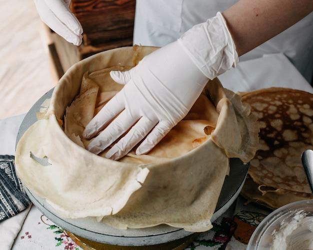 Pâte à l'intérieur du moule rond avec cuisinier étalant des tranches dessus à l'intérieur de la cuisine