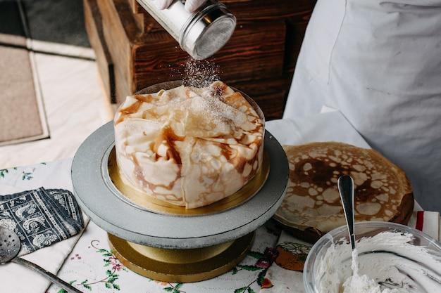 Pâte à l'intérieur de la poêle ronde avec cuisinier étalant des tranches de cuisson des repas sur elle à l'intérieur de la cuisine