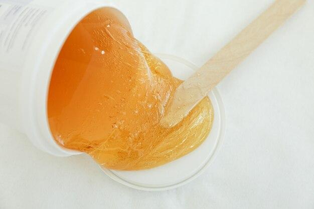 Pâte jaune liquide pour shugaring sur blanc. épilation et soins corporels