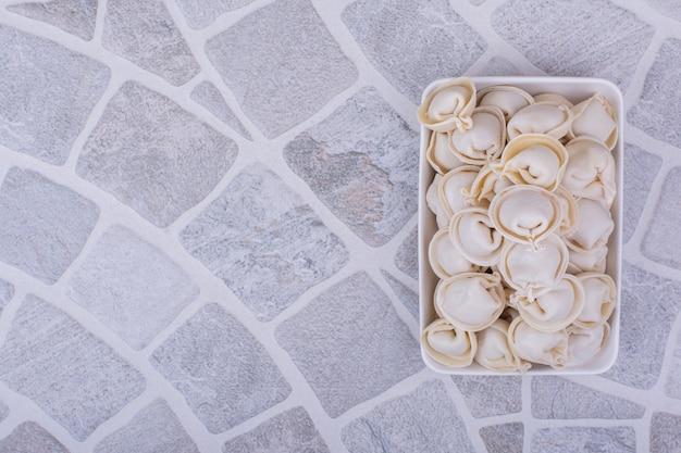 Pâte khinkali caucasienne dans un bol blanc sur une surface grise