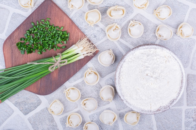 Pâte khinkali du caucase sur une planche de bois avec des oignons verts