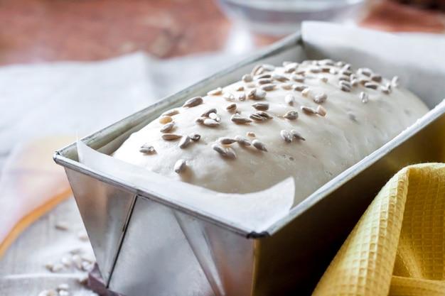Pâte de levure crue sous forme d'étain, prête à cuire du pain avec des graines de tournesol