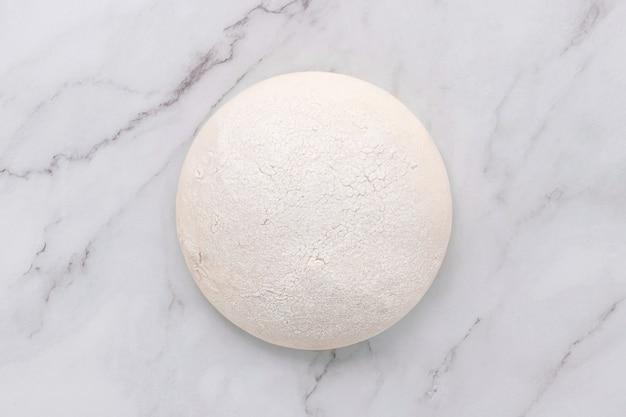 Pâte à levure fraîche et crue faite maison reposant sur une table en marbre à plat.