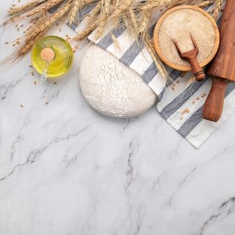 Pâte à levure fraîche faite maison reposant sur une table en marbre avec des épis de blé et un rouleau à pâtisserie.