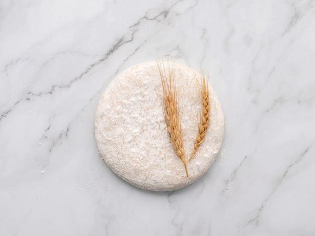 Pâte à levure fraîche faite maison reposant sur une table en marbre à plat.