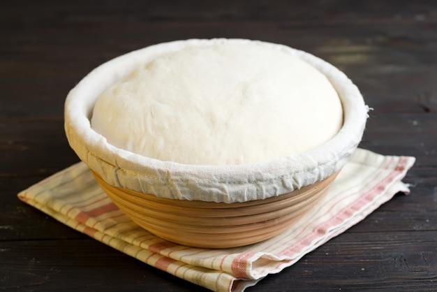 Pâte à levure fraîchement cuite dans un panier pour la cuisson de gâteaux et de biscuits naturels frais sur un fond en bois foncé.