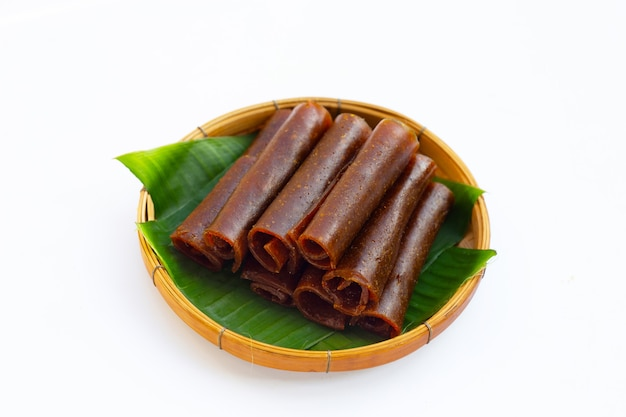 Pâte de mangue séchée dans un panier en bambou sur fond blanc.