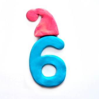 Pâte à modeler bleue, numéro 6 six dans un bonnet d'hiver rouge sur fond blanc