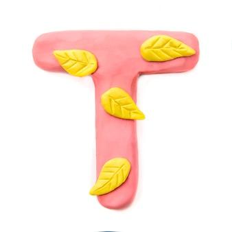 Pâte à modeler rose lettre t de l'alphabet anglais avec des feuilles d'automne jaunes