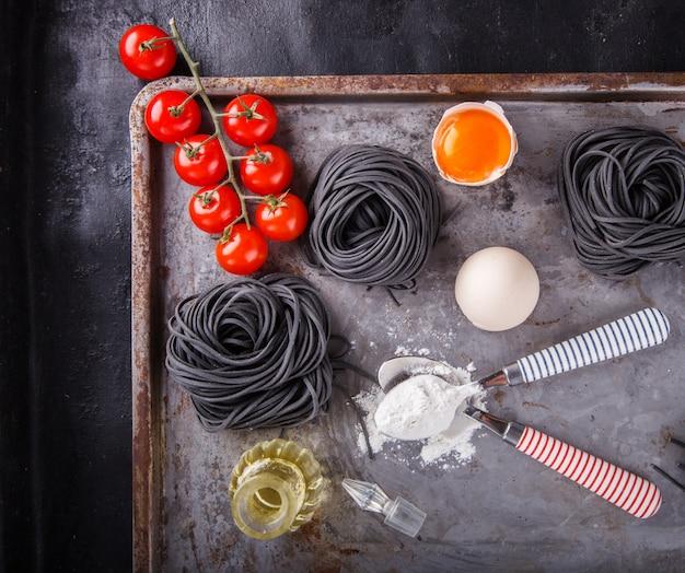 Pâte noire brute et les ingrédients sont faits maison, spaghetti