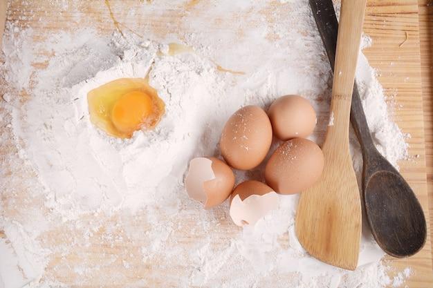 Une pâte avec des oeufs et des ustensiles.