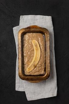 Pâte à pain aux bananes crues dans un plat de cuisson rectangulaire sur fond noir