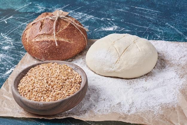 Pâte et pain cuit sur table bleue.