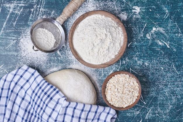 Pâte à pain avec des ingrédients sur table bleue.