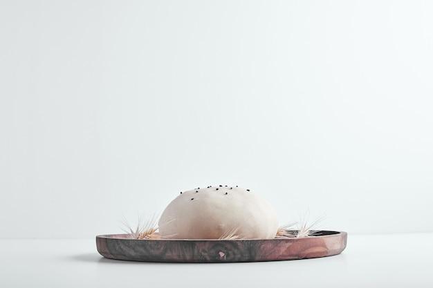 Pâte à pain ronde à la main dans un plateau en bois, vue latérale.