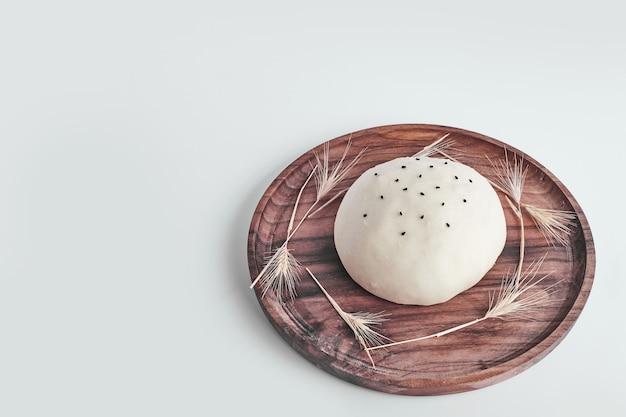 Pâte à pain ronde à la main dans un plateau en bois.