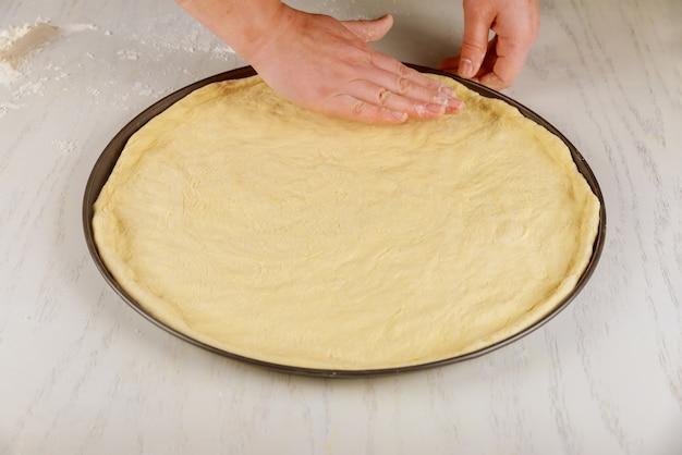 Pâte à pizza crue fraîche dans le moule du four.