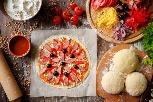 Pâte à pizza avec des ingrédients sur bois