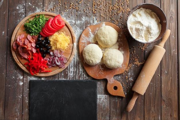 Pâte à pizza avec des ingrédients sur la table en bois