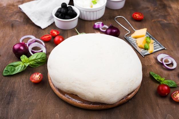 Pâte à pizza et légumes high angle
