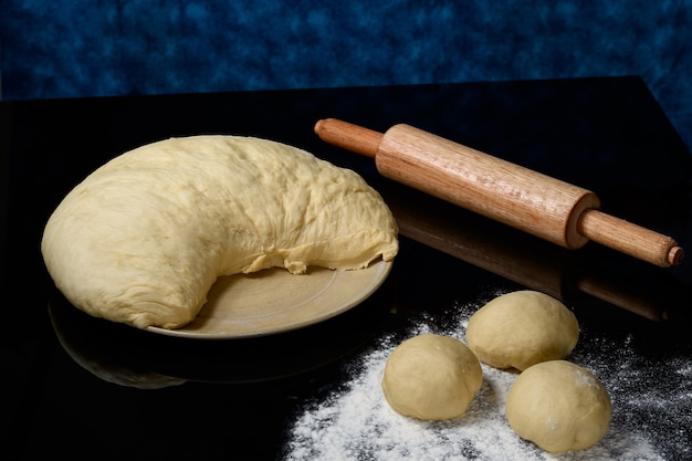 Pâte pour la préparation du pain et des biscuits, reposant sur une surface sombre et réfléchissante