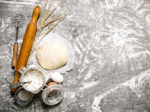 Pâte préparée. la pâte et l'ingrédient pour lui. sur la table en pierre. espace libre pour le texte. vue de dessus