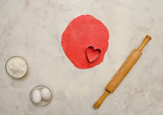 Pâte rouge avec un cœur découpé, un rouleau à pâtisserie, des œufs et de la farine sur un tableau blanc. vue de dessus, espace pour le texte