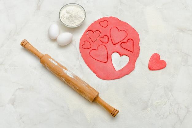 Pâte rouge avec un rouleau à pâtisserie et des coeurs découpés