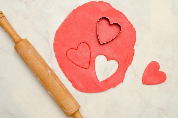 Pâte rouge avec un rouleau à pâtisserie et découper des coeurs sur un tableau blanc, gros plan
