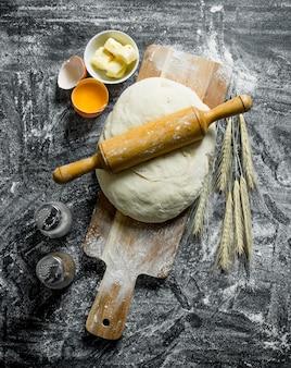 La pâte avec un rouleau à pâtisserie, des épillets et des épices. sur surface rustique