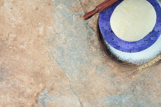 Pâte avec rouleau à pâtisserie et farine sur table en marbre.