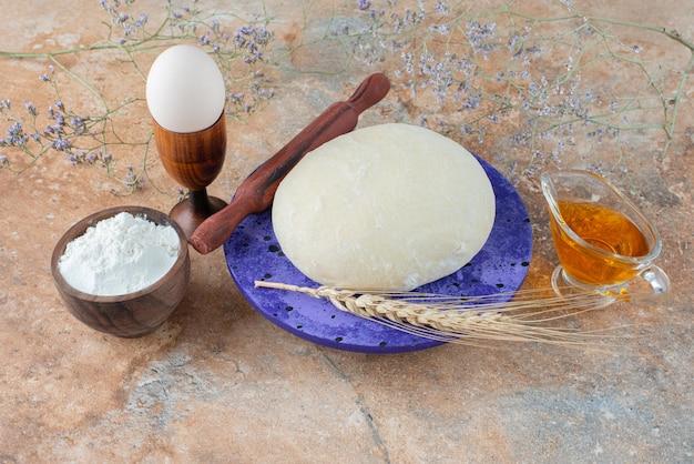 Pâte avec rouleau à pâtisserie et oeuf sur marbre