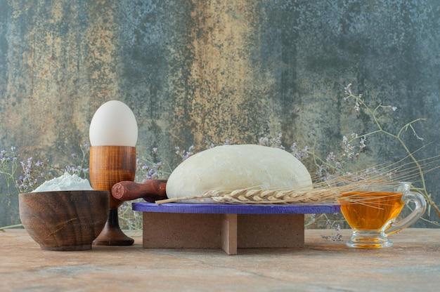 Pâte avec rouleau à pâtisserie et oeuf sur table en marbre.